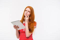 Pensive beautiful young woman thinking and holding tablet Royalty Free Stock Photo