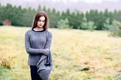 Pensive beautiful young woman in woolen sweater Royalty Free Stock Images