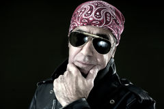 Pensive biker. With leather jacket, sunglasses and bandana Royalty Free Stock Photography