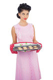 Pensive black hair model holding baking tray of cookies Royalty Free Stock Photos