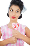 Pensive black hair model holding a heart shaped lollipop Royalty Free Stock Photo