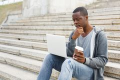 Pensive black man using laptop outdoors. Pensive african-american man working outdoors on laptop. Preparing for exams, sitting on stairs at university campus Stock Image