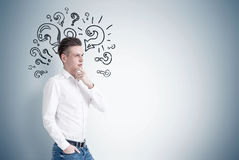 Pensive blond businessman, question marks Stock Photography
