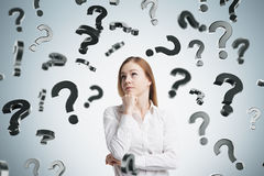 Pensive blond girl and falling question marks Stock Photos