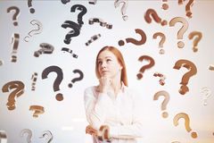 Pensive blond girl, falling question marks Royalty Free Stock Image