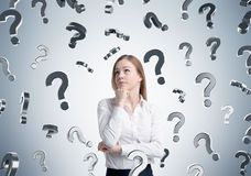 Pensive blond girl and question marks, gray Royalty Free Stock Images