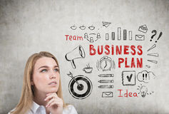 Pensive blond woman and business plan Stock Photography