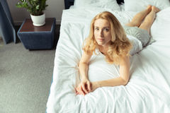 Pensive blond woman lying on bed at home Stock Image
