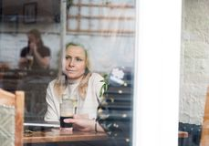 Pensive blonde attractive young adult single woman in pub. Pensive blonde attractive young adult single women in pub. Shot through window with reflections on royalty free stock images