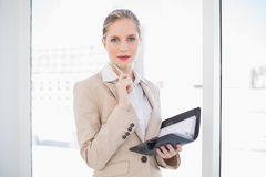 Pensive blonde businesswoman holding datebook Stock Images