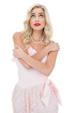 Pensive blonde model in pink dress posing holding her shoulders and looking up Royalty Free Stock Image