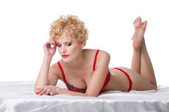 Pensive blonde in red lingerie lying on bed Royalty Free Stock Image
