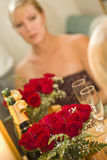 Pensive Blonde Sits at Mirror Near Champagne and Roses Royalty Free Stock Photos