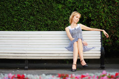Pensive blonde sitting on bench Royalty Free Stock Photography