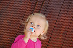 Pensive blue-eyed baby toddler happy with pacifier. Happy blond blue-eyed baby toddler with pacifier closeup royalty free stock image