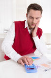Pensive bookkeeper working with graphs at desk at office. Royalty Free Stock Photos
