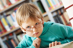 Pensive boy. Portrait of clever boy thinking in library Royalty Free Stock Image