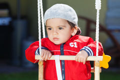 Pensive boy. Pensive arabic boy swinging outdoors stock photo