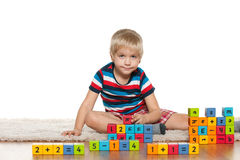 Pensive boy with blocks on the floor Royalty Free Stock Image
