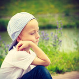 Pensive boy child thinking and daydreaming. Thoughtful kid leaning on his hand looking forward. Imagination Royalty Free Stock Images