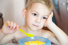 Pensive boy eating Stock Image