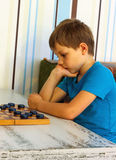 Pensive boy during a game of checkers Stock Photography