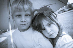 Boy and girl under umbrella. Pensive boy and girl under umbrella in black and white stock image