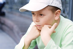 Pensive boy in green Stock Images