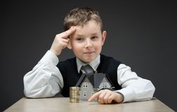 Pensive boy with home model and pile of coins Stock Photography