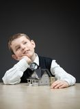 Pensive boy with house model and pile of coins Stock Image