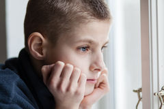 Pensive Boy Leans his Face on Hands at the Window Stock Images