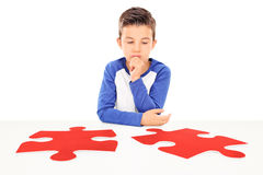 Pensive boy looking at two pieces of puzzle Royalty Free Stock Photos