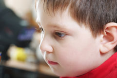 Pensive boy in red Stock Images