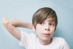 Pensive boy scratches back of his head Stock Images