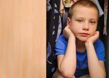 Pensive boy sitting in a closet. Pensive boy sitting in closet royalty free stock images