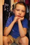Pensive boy sitting in closet. Pensive boy sitting in a closet royalty free stock image