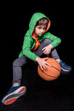 Pensive boy sitting on floor with basketball ball and looking away Royalty Free Stock Images