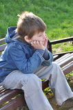 Pensive boy sitting on a park bench Stock Photos