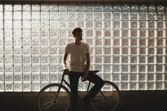 Pensive boy standing with classic bicycle and thoughtfully looking aside posing on camera. Portrait of young man in. Pensive boy standing with classic bicycle Stock Photo