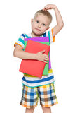 Pensive boy in striped shirt with books Royalty Free Stock Image