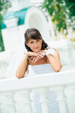 Pensive bride in white dress has leant elbows on handrail Royalty Free Stock Photos