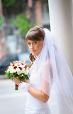 Pensive bride in white dress standing and holding roses bouquet Stock Photography
