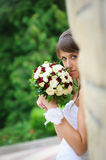 Pensive bride in white dress standing and holding roses bouquet Royalty Free Stock Photography