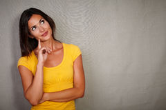 Pensive brunette lady thinking while looking away Royalty Free Stock Image