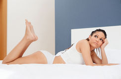 Pensive brunette woman resting in her bed Royalty Free Stock Photos