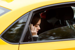 Pensive brunette woman riding in taxi and talking on phone Stock Images