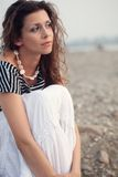 Pensive brunette woman sitting on coast Stock Images