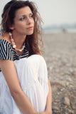 Pensive brunette woman sitting on coast. Beautiful pensive brunette woman sitting on coast Stock Images