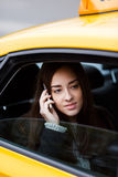 Pensive brunette woman talking on phone sitting in yellow taxi Royalty Free Stock Photo