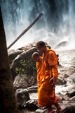 Pensive  Buddhist monks  walking around waterfall. Pensive  Buddhist monks  walking near waterfall Stock Images